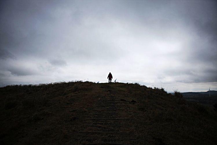 People walking on landscape against cloudy sky