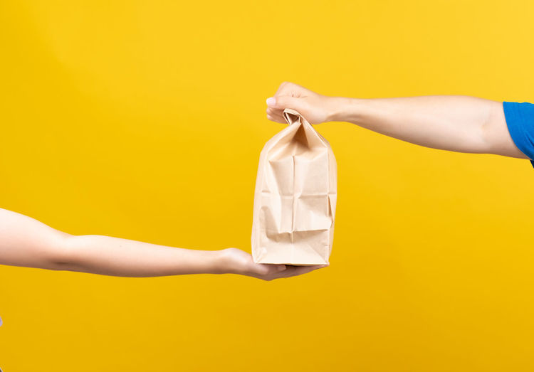 Midsection of woman holding paper against yellow background