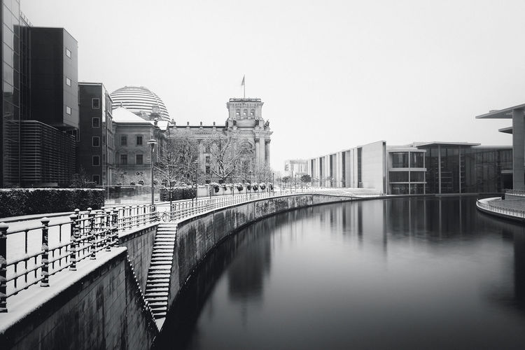 Reichstag building by river against clear sky