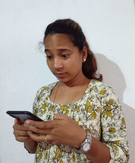 Portrait of young woman using phone while standing against wall