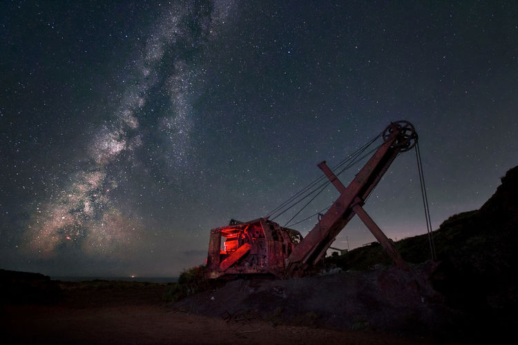 Low angle view of abandoned crane against sky at night