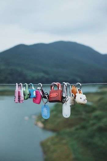 Key Together Couple Hanging Mountain Focus On Foreground No People Water Day Nature Multi Colored Lake Decoration Outdoors Art And Craft Sky Creativity Waterfront Mountain Range Close-up