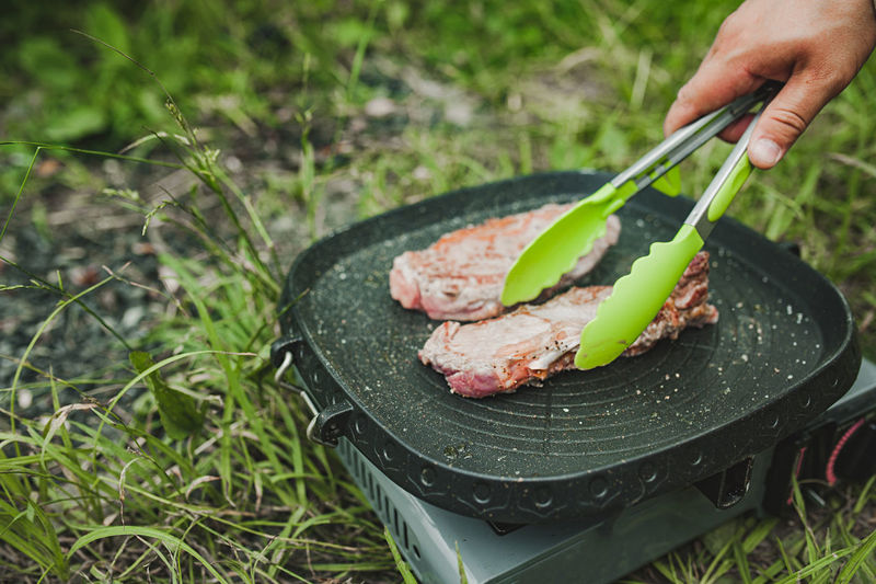 Meat steak fried grill pan on gas stove open air, hand turns over potholders appetizing piece meat