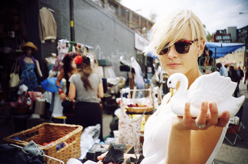 Side view portrait of woman holding swan figurine while standing in market