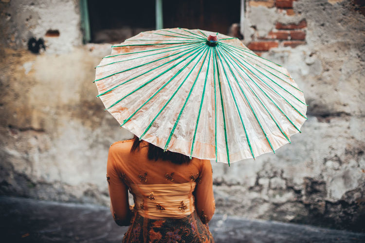 Rear view of woman with umbrella in old town
