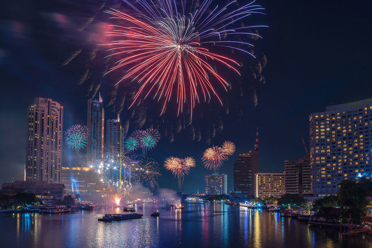 Firework display over river by buildings against sky at night