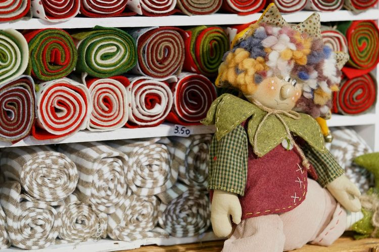 Close-Up Of Stuffed Toy By Rolled Up Fabrics In Shelves At Store For Sale