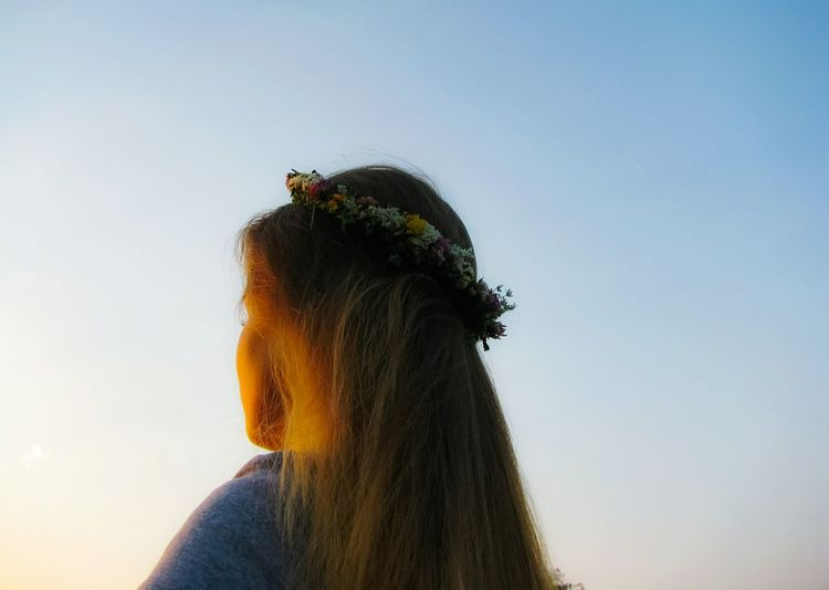 Low angle view of woman wearing wreath against sky