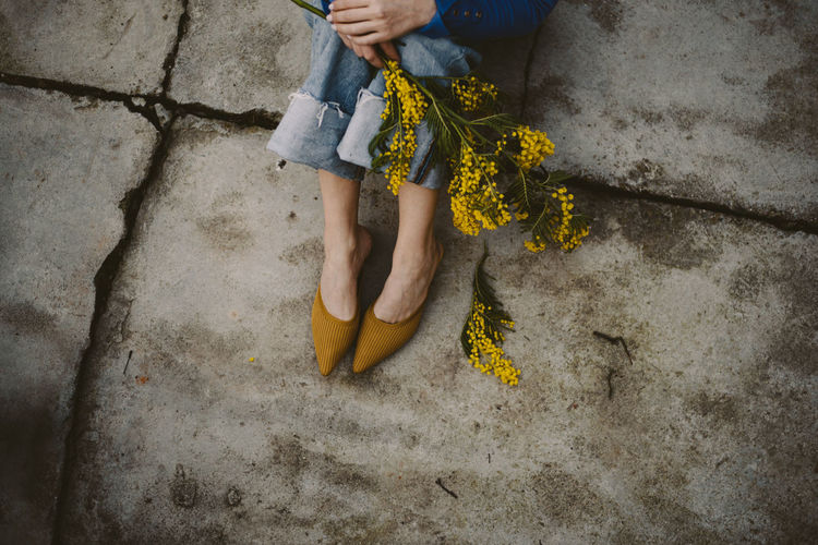 Low section of woman sitting on the floor with yellow flower