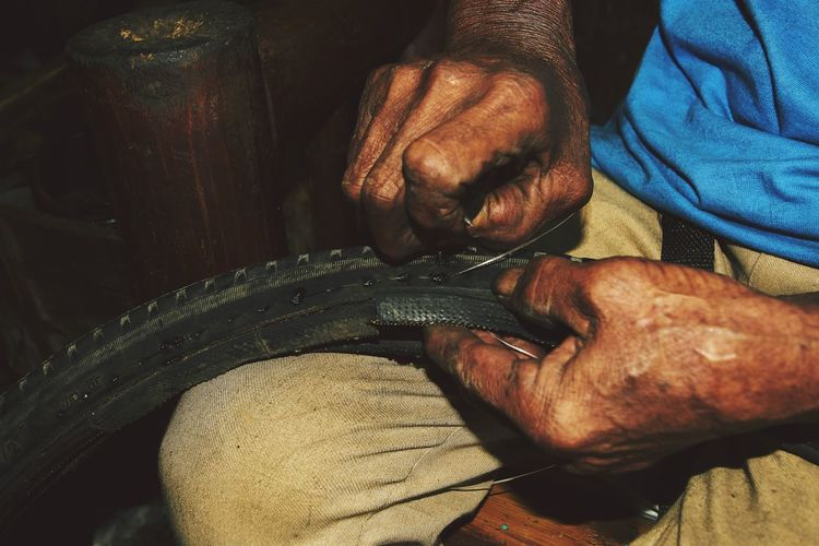 Midsection of man working on tire