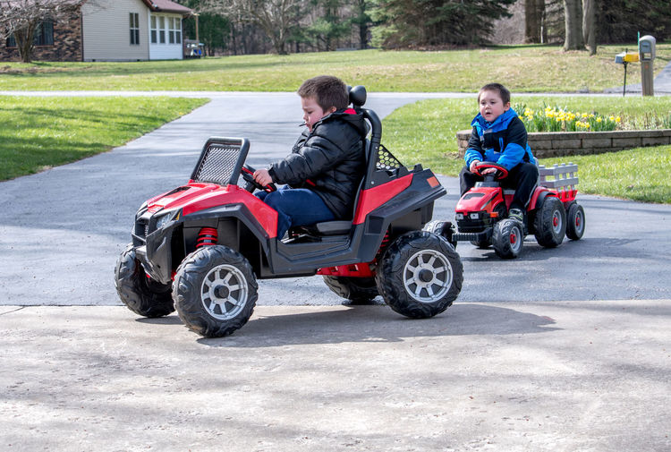 Boys Riding Toy Vehicles On Road