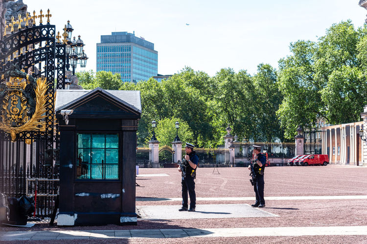 Armed policemen guarding the gates of Buckingham Palace a sunny day at springtime Brexit Britain Buckingham Buckingham Palace London Queen Uk United Kingdom Antiterrorism Architecture Blue British Building Capital City Culture Destinations Elizabeth England English Europe European  Famous Guard Guarding Guards Historic History KINGDOM Landmark Monarchy Old Palace People Police Policemen Protection Royal Royalty Security Sightseeing Sunny Terrorism Tourism Tourist Traditional Travel United Westminster