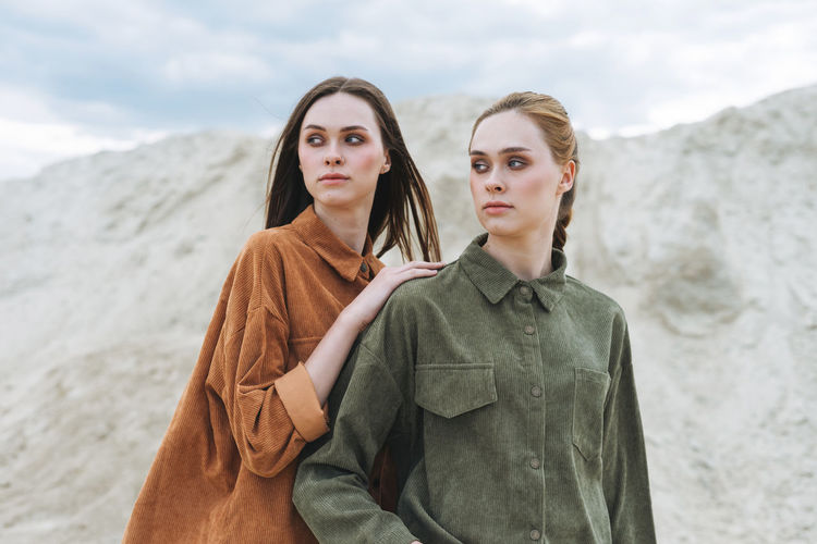 Fashion beauty portrait of young women sisters in brown organic velvet shirts on desert background