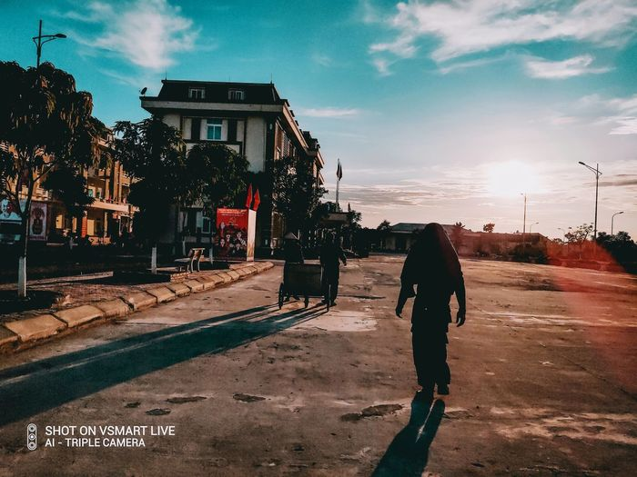 Full length of man walking on street against buildings in city
