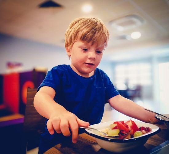 Boy having fruit at table