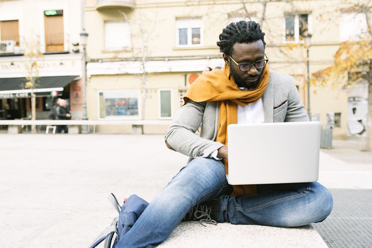 Young Man Using Laptop While Sitting In City
