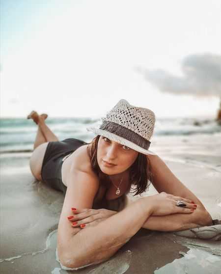 Portrait of woman wearing hat lying at beach against sky