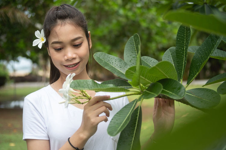 Young woman holding leaves outdoors