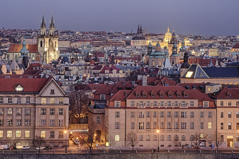 View of illuminated buildings in city of prague at dusk