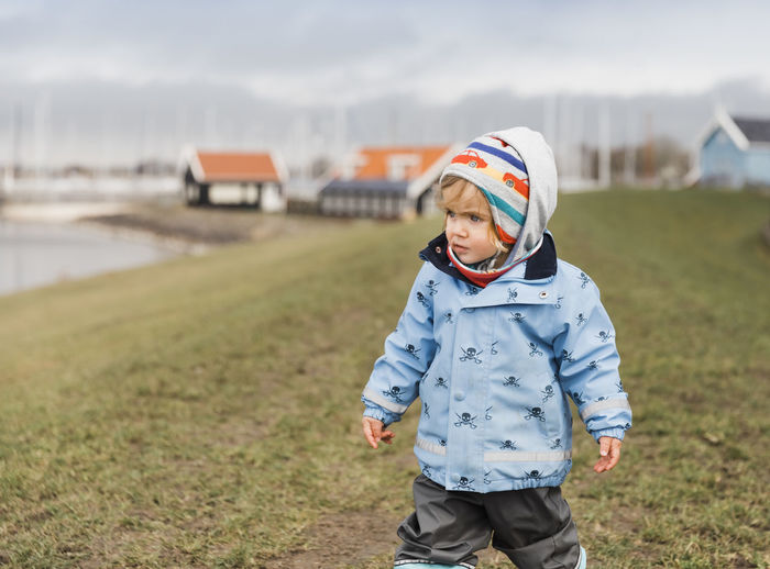 Cute Girl Wearing Warm Clothes While Walking On Field During Winter