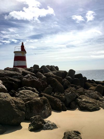 Rocks and lighthouse at beach