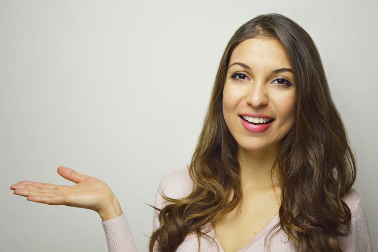Showing Product To Customer Ads Beautiful Woman Cheerful Close-up Gesturing Hand Showing Happiness Headshot Indoors  Long Hair Looking At Camera One Person One Woman Only One Young Woman Only Only Women Portrait Showing Smile Girl Smiling Studio Shot White Teeth Young Adult Young Woman Smiling Young Women