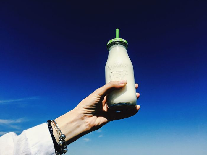 Cropped Image Of Woman Holding Milk Bottle Against Blue Sky On Sunny Day