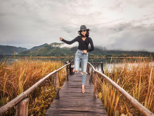 Asian woman is dancing on an old wooden bridge. Alone Amazing Beautiful Beauty In Nature Bridge Cloud Cloud - Sky Dancing Floor Happy Jumping Lake Lifestyles Love Meadow Memory Nature Nature Outdoors Portrait Reeds Summer Woman Wonderful