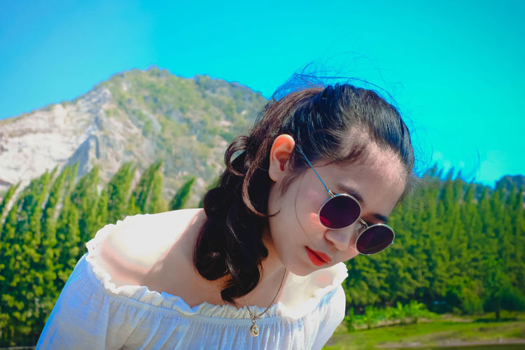 Portrait of woman with sunglasses against mountain