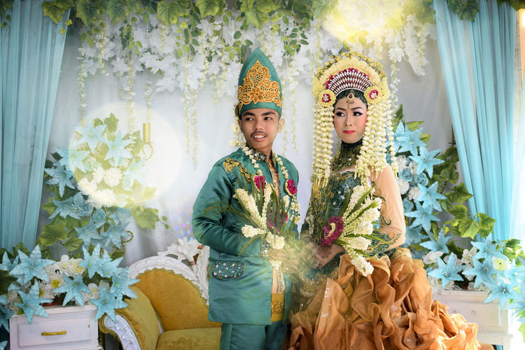 Smiling young couple holding flowers standing during wedding reception