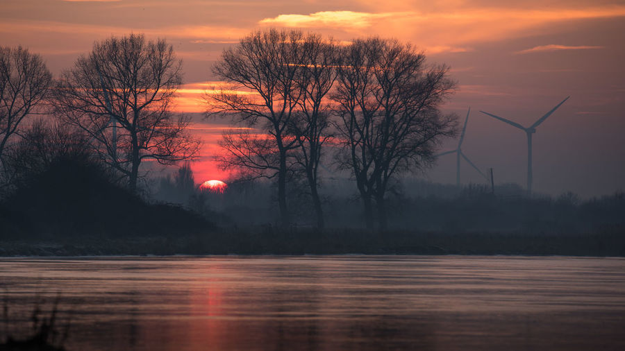 Dutch country side with setting sun and wind turbines and a traditional wind mill on the horizon 16x9 Cloud - Sky Copy Space Dusk Environment Lake Landscape Nature Nature No People Outdoors Pink Reflection Silhouette Sky Sunset Technology Tree Water Wind Mill Wind Turbine Zeeland