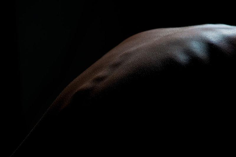 Cropped Image Of Human Back Against Black Background