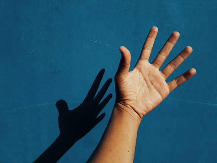 High angle view of human hand against blue wall