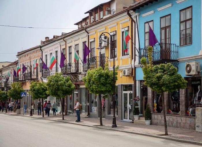 People on street by buildings in city against sky