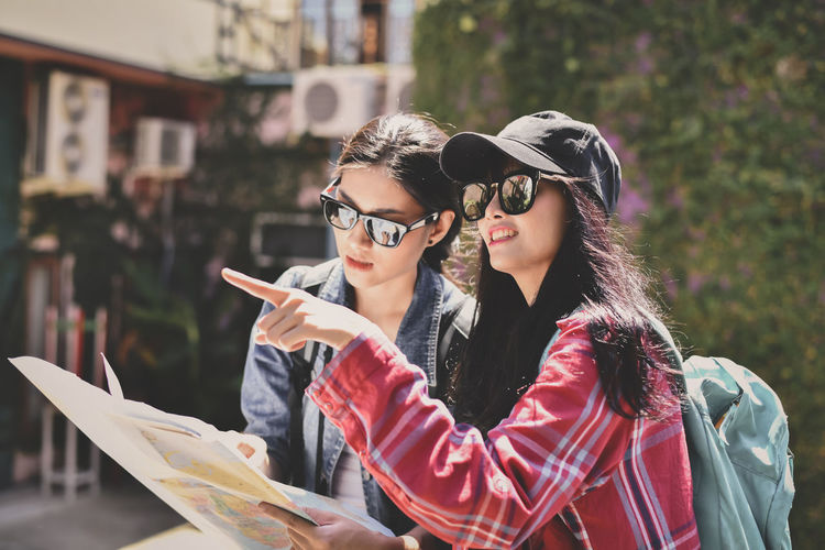 Woman reading map while friend pointing in city