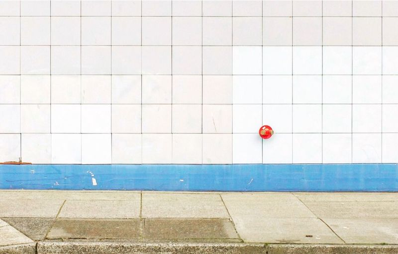 Red umbrella on wall by swimming pool