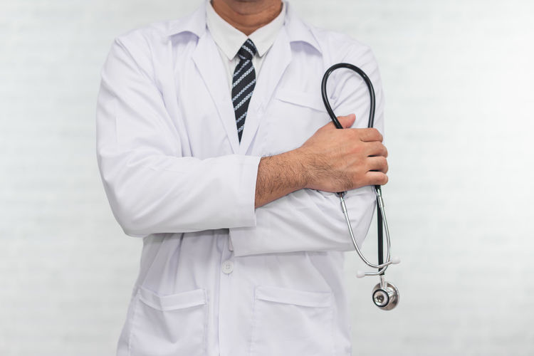 Midsection of doctor standing against wall