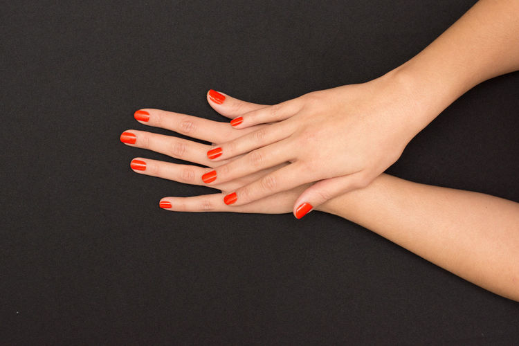 Cropped Hands With Red Nail Polish Against Black Background