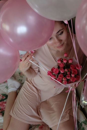 High angle view of woman holding balloons at home