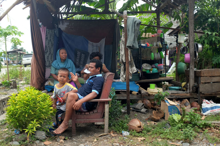 victim of the earthquake and tsunami, sits at their temporary shelter in Palu, Central Sulawesi, Indonesia Palu Earthquake And Tsunami 2018 Victims INDONESIA Shelter Child Childhood Males  Men Sitting Full Length Group Of People Togetherness Looking At Camera Women Casual Clothing Portrait Family Boys Bonding Plant Real People Leisure Activity Females Girls Outdoors Son Sister Innocence Daughter Autumn Mood