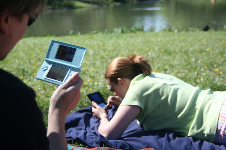 Friends playing video games while relaxing in park