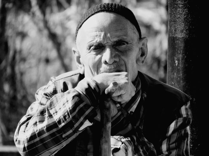 Portrait of senior man sitting against trees