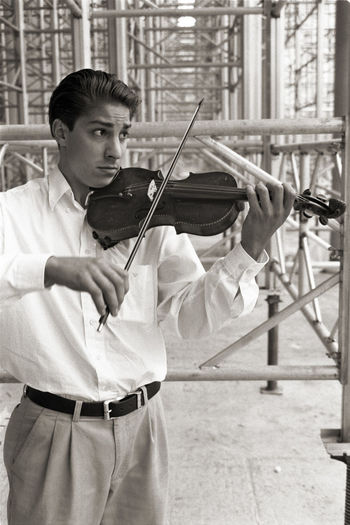 Man playing violin while standing on footpath against scaffolding