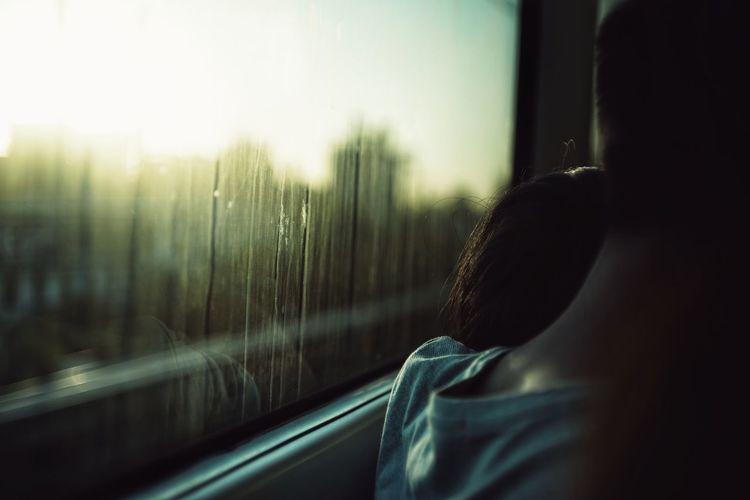 Rear view of man looking through train window