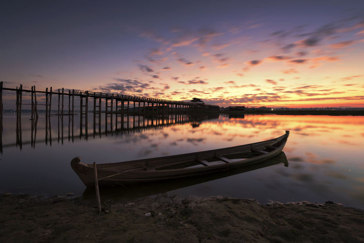 Wooden pier over sea against dramatic sky during sunset