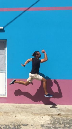 Side View Of Man Levitating Against Colorful Wall On Sunny Day
