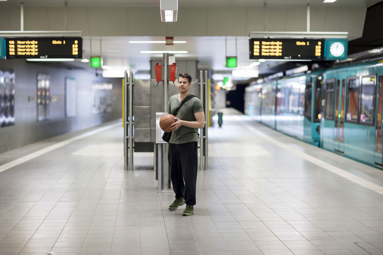 Handsome athletic man with a basketball in one hand waiting for the subway train and posing for the camera. Adult Athletic Basketball Long Shot Man Signage Bag Ball Casual Clothing Caucasian Ethnicity Model Platform Posing For The Camera Shoulder Bag Sports Sports Bag Sporty Strap Subway Subway Station Sweatpants T-shirt Train Urban V-neck