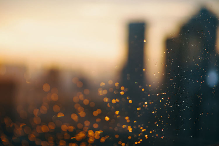 Defocused image of city against sky during sunset