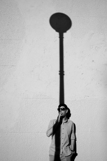 Young Man Smoking While Standing On Wall During Sunny Day