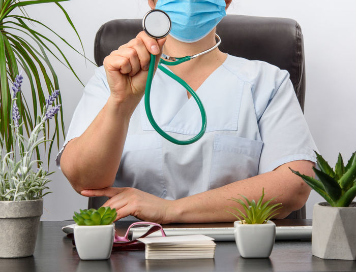Midsection of doctor wearing mask holding stethoscope at clinic